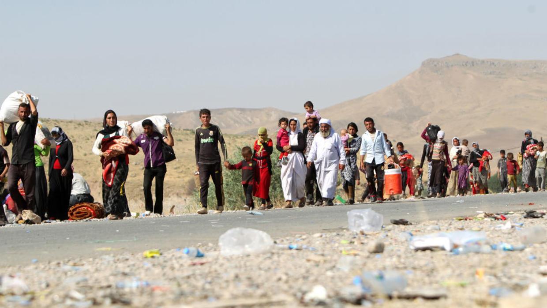"""نزوح آلاف العائلات العراقية من الطائفة الأيزيدية في آب / أغسطس 2014 ، هرباً من عنف تنظيم """"الدولة الإسلامية""""."""