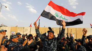 Un miembro de la policía federal iraquí agita una bandera iraquí mientras celebran la victoria de las operaciones militares contra el grupo Estado Islámico en Mosul (Imagen de archivo - 2 de julio de 2017).