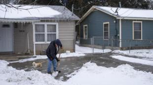مواطن يجرف الثلج من أمام منزله في واكو بولاية تكساس، في 17 شباط/فبراير 2021