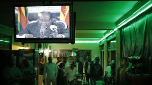 Ciudadanos de Harare, la capital de Zimbabue, observan el discurso televisivo del presidente Robert Mugabe, quien se dirigió a la nación la noche del domingo 19 de noviembre y no renunció a su cargo.