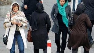 A file picture taken on February 7, 2018 shows Iranian women wearing hijab walk down a street in the capital Tehran