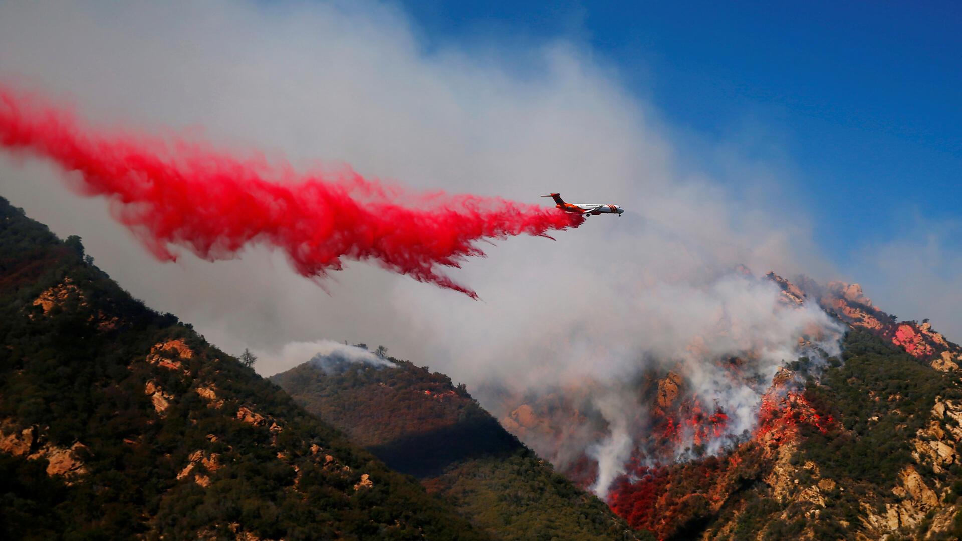 Una aeronave intenta sofocar las llamas del Woolsey Fire mientras continúa ardiendo en Malibu, California.