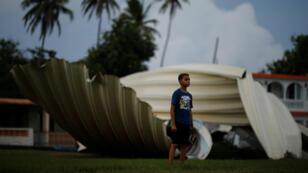 Un niño juega beísbol en la población de Loaiza, Puerto Rico, una de las zonas devastadas por el paso del huracán María y que ha mostrado pocos avances a un año de la tragedia.