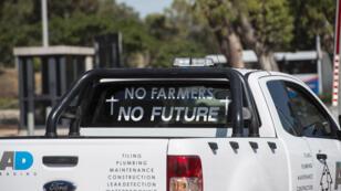 Voiture affichant un slogan contre les expropriations agricoles en Afrique du Sud.
