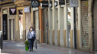 امرأة تضع كمامة للوقاية من فيروس كورونا في شارع ببالما دي مايوركا، إسبانيا، 10 نيسان/أبريل 2020.