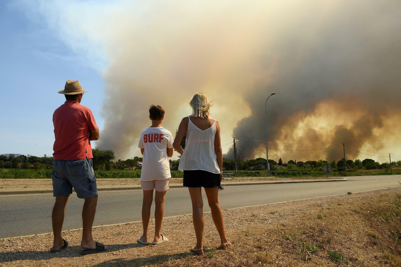 Los turistas observan desde el borde de la carretera el denso humo que oscurece el cielo de los incendios forestales reavivados al norte de Grimaud, en el departamento de Var, al sur de Francia, el 18 de agosto de 2021.