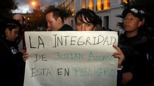 """A protester outside the Foreign Ministry in Quito, Ecuador holds a placard reading """"Assange's Safety is in Danger,"""" after British police took WikiLeaks founder Julian Assange out of Ecuador's embassy in London and arrested him"""