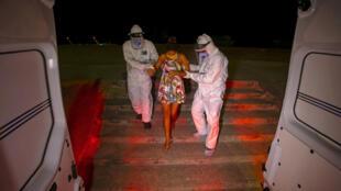 Trabajadores de la Secretaría Especial de Salud Indígena trasladan a Janete Vasconcelos da Silva, de 19 años de edad, una mujer indígena de la tribu Tupinamba, embarazada de 8 meses y a la que se le ha diagnosticado el nuevo coronavirus, COVID-19, a una ambulancia para llevarla a un hospital de Santarem, en el estado de Pará (Brasil), el 17 de julio de 2020.