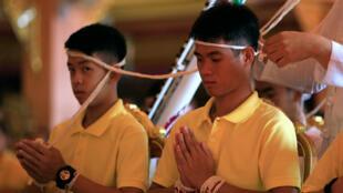 Dos niños del equipo de fútbol rescatado de una cueva en Tailandia asisten a una ceremonia religiosa, en un templo en Mae Sai, en la provincia norteña de Chiang Rai, Tailandia el 19 de julio de 2018.