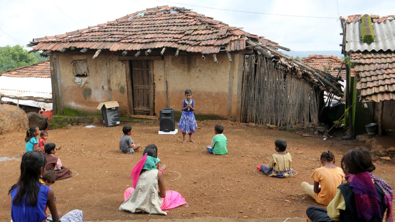 Ante la imposibilidad de conectarse a las clases en línea, un grupo de niños escuchan una clase pregrabada en el poblado de Dandwal, estado de Maharashtra, India, el 23 de julio de 2020