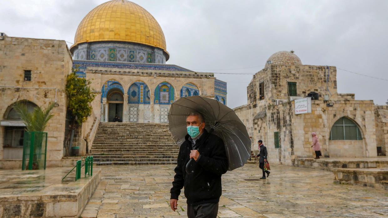 فلسطيني يضع كمامة وقائية من فيروس كورونا المستجد يسير أمام مسجد قبة الصخرة في القدس الشرقية المحتلة في 20 آذار /مارس 2020
