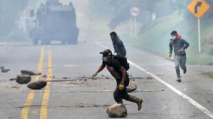 Manifestantes indígenas corren durante un enfrentamiento con el escuadrón antidisturbios de la policía en la vía Panamericana, Cauca, Colombia. 19 de marzo de 2019.