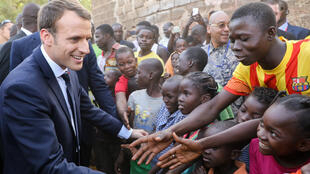 Emmanuel Macron salue des enfants, le 28 novembre 2017, après avoir visité une école de Ouagadougou, au Burkina Faso.