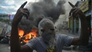 A masked demonstrator gestures before burning tires during protests in Port-au-Prince, on February 10, 2019