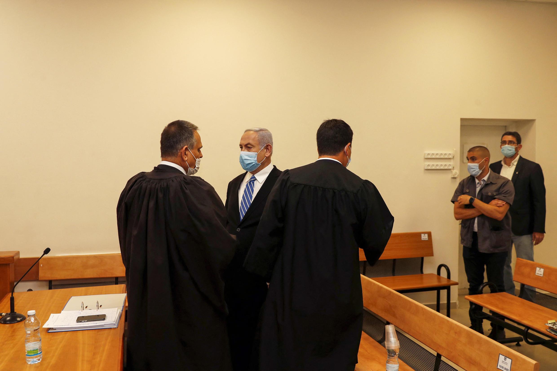 Le Premier ministre israélien Benjamin Netanyahu (2e-L), portant un masque protecteur, est photographié à l'intérieur d'une salle d'audience du tribunal de district de Jérusalem le 24 mai 2020, au cours de la première journée de son procès pour corruption.