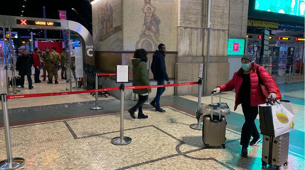 Una mujer con una máscara protectora camina con sus equipajes dentro de la estación principal de trenes de Milán mientras las autoridades italianas se preparan para bloquear Lombardía para evitar la propagación del coronavirus altamente infeccioso en Milán, Italia, el 7 de marzo de 2020.