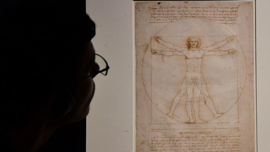 """En esta imagen de archivo, tomada el 13 de mayo de 2015, un visitante observa  la famosa obra """"El Hombre de Vitruvio"""" de Leonardo Da Vinci en Milán, Italia."""