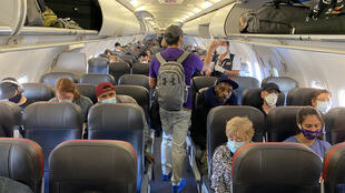 Esta imagen de archivo muestra a pasajeros, la mayoría de ellos con mascarillas sanitarias, de un vuelo de American Airlines con destino a Charlotte, el 3 de mayo de 2020 en Nueva York