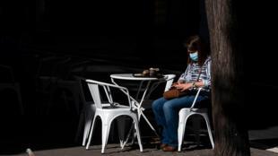 Una mujer con mascarilla, sentada en la terraza de un bar el 19 de mayo de 2020 en la ciudad española de Valencia