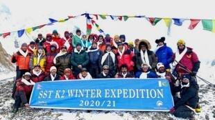 Montañeros y sherpas posan para fotografías después de llegar a la cima del monte K2, la segunda montaña más alta del mundo, en el campamento base de la expedición de invierno, en la región de Gilgit-Baltistan en el norte de Pakistán, el 16 de enero de 2021.