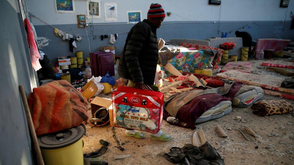 Una migrante transporta sus pertenencias en el centro de detención golpeado por un ataque aéreo en el suburbio de Tajoura en Trípoli, Libia, el 3 de julio de 2019.