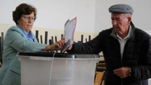 Un hombre, con el apoyo de una jurado de votación, deposita su voto en un colegio electoral de Pristina, Kosovo, el 6 de octubre de 2019.