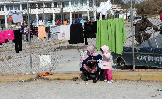 Une mère et sa fille devant les grillages à l'entrée du camp de Hellenikon.