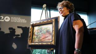 """Sylvie Sulitzer, la petite-fille du collectioneur, posant devant le tableau de Renoir intitulé """"Deux femmes dans un jardin""""."""