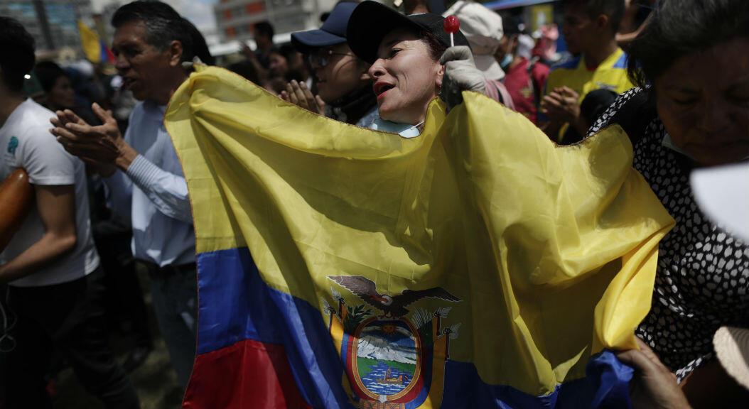 Un grupo de personas celebra con banderas tras el acuerdo alcanzado entre el presidente, Lenín Moreno, y el movimiento indígena este 14 de octubre, en Quito. La capital ecuatoriana comienza a recuperar la normalidad.
