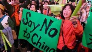 """Une militante du parti de la présidente sortante Tsai Ing-wen tenant une pancarte """"Non à la Chine"""" lors du meeting du 10 janvier 2020."""