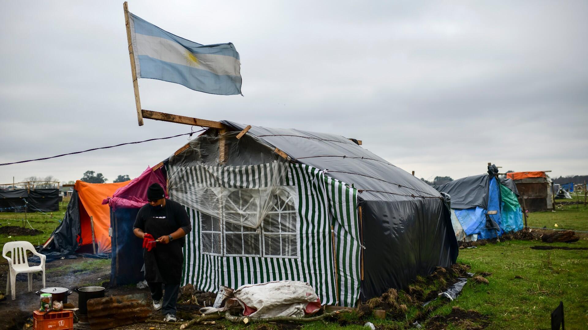 Un hombre cocina mientras una bandera argentina ondea en el viento sobre una carpa instalada en un terreno ocupado por personas sin hogar, en las afueras de Guernica, en la provincia de Buenos Aires, Argentina, el 28 de agosto de 2020.