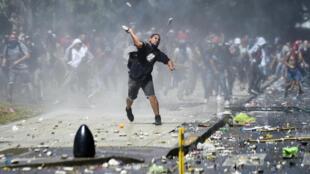 Un manifestant jetant un projectile en direction des forces de l'ordre lors du rassemblement contre la réforme des retraites, le 18 décembren à Buenos Aires.