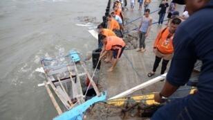 Miembros de la Guardia Costera mientras transportaban los restos de un bote que se hundió frente a la costa de la isla de Guimaras en Filipinas el 4 de agosto de 2019.