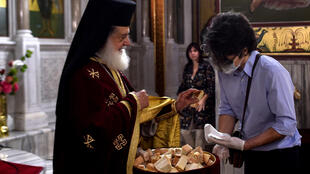 A priest gives the Holy Bread to a worshiper wearing a protective face mask and gloves in a church of Thessaloniki on May 17, 2020, as churches in Greece reopened after a two-month-long closure aimed at slowing the spread of Covid-19.