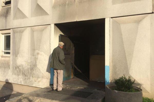 Un résident du foyer constate l'étendue des dégâts. L'incendie a ravagé l'entrée.