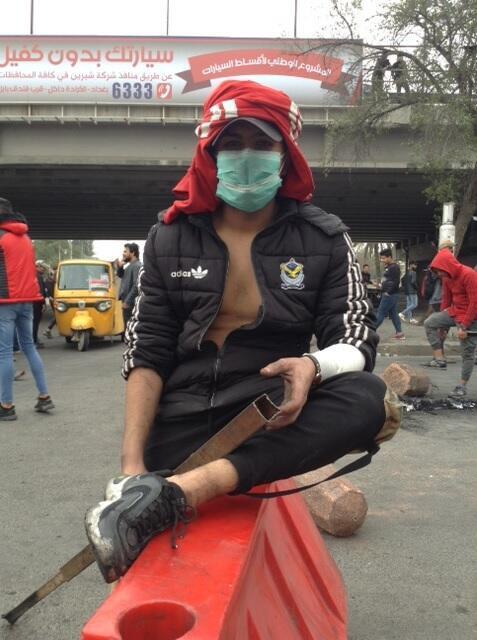 متظاهر عراقي شاب يحاول قطع الطريق السريع بقضبان حديدية. 19 يناير 2020.