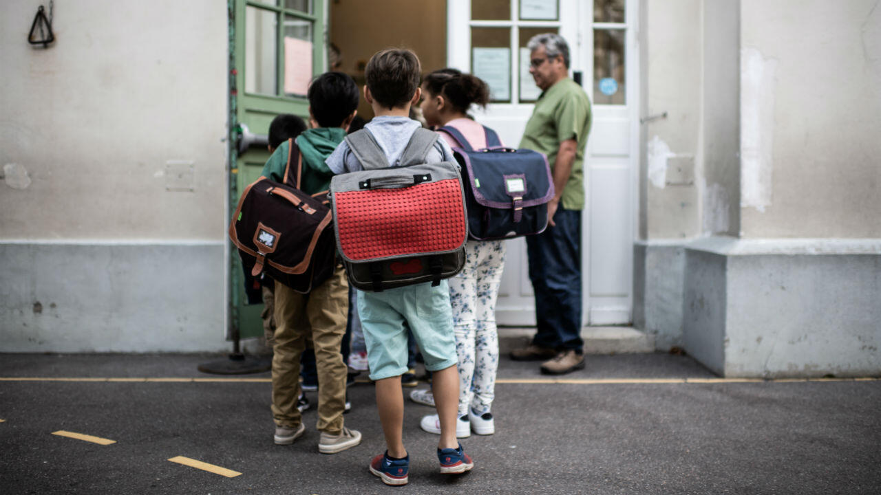 Children enter their classroom on the first day of the 2019 school year at an elementary school in Paris.