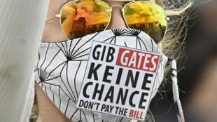 """إحدى المشاركات في تظاهرة ضد بيل غيتس في 16 تموز/يوليو 2020 تضع كمامة كتب عليها """"لا تعطوا أية فرصة لغيتس"""""""