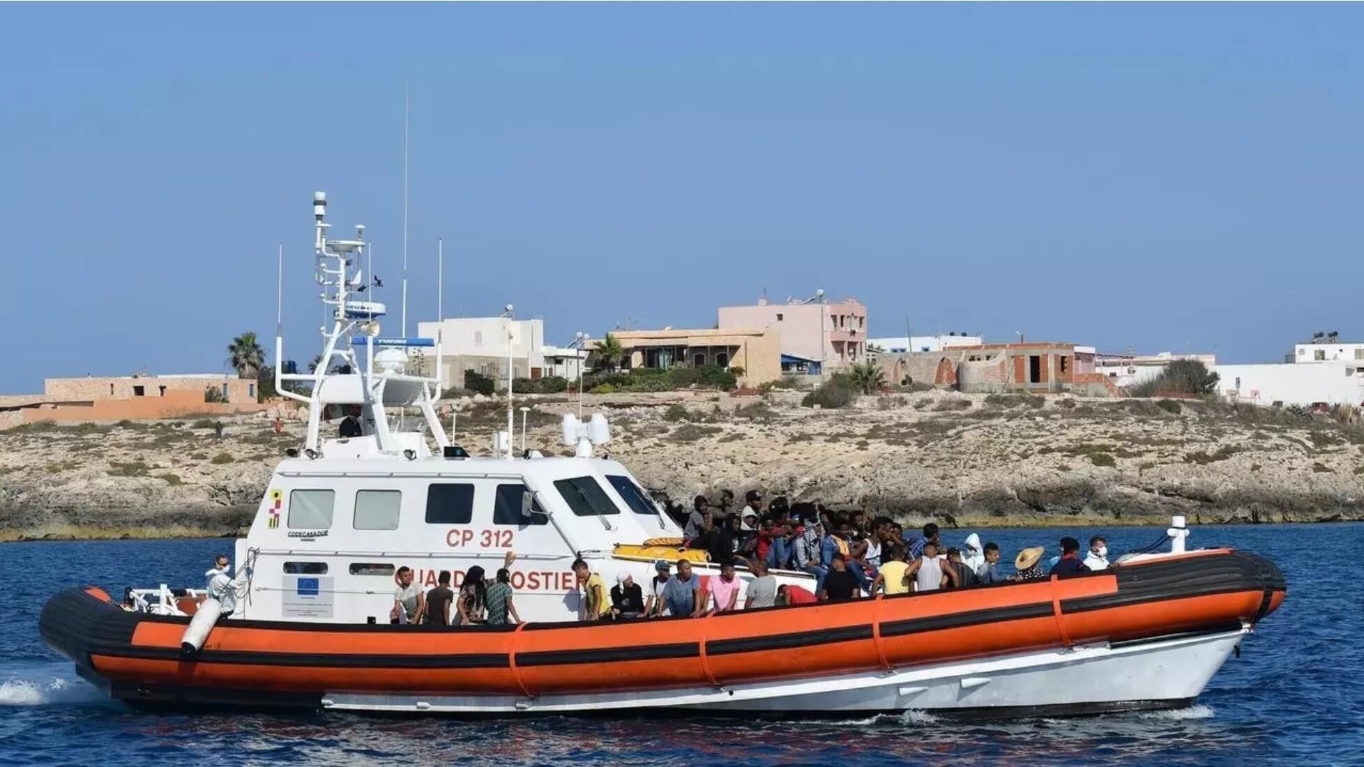 Migrantes de Túnez y Libia llegan a bordo de un barco italiano de la Guardia Costiera a la isla de Lampedusa el 1 de agosto de 2020.