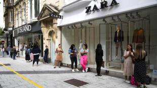 Clientes esperan frente al escaparate de Zara, en la ciudad de Cardiff, Reino Unido, el 22 de junio de 2020