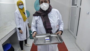 A healthworker in a clinic in Blida, in the centre of Algeria, takes out the Sputnik V Covid-19 vaccine from a refrigerated storage unit.