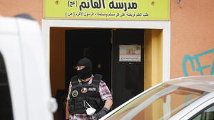 A police officer walks out of Al-Irschad Mosque during a raid in Berlin, as dozens of police and special forces stormed mosques and associations linked to Hezbollah in Bremen, Berlin, Dortmund and Muenster early Thursday.