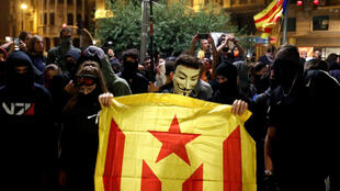 A masked Catalan pro-independence demonstrator holds an Estelada (Catalan separatist flag) during a protest against police action, outside the National Police headquarters, in Barcelona, Spain, October 26, 2019