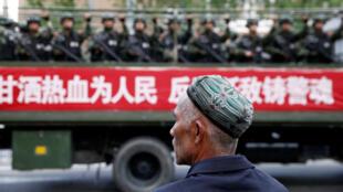 Un homme ouïghour observe un camion transportant des policiers dans la région du Xinjiang, en 2014.