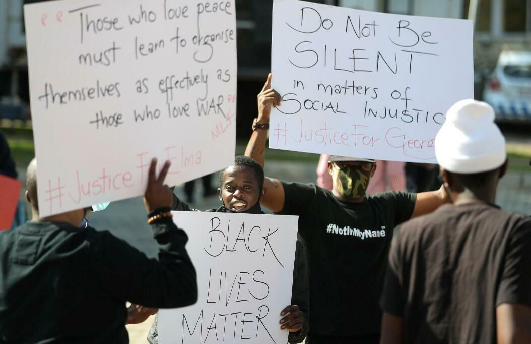 """Manifestantes con mensajes como """"No permanezcas en silencio en asuntos de injusticia social"""", frente a la embajada de EE. UU., en Pretoria, Sudáfrica, el 6 de junio de 2020."""