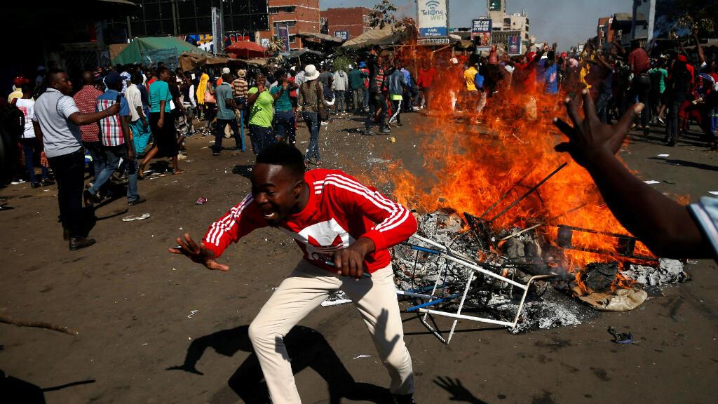 Los partidarios del opositor Movimiento por el Cambio Democrático (MDC) de Nelson Chamisa reaccionan cuando bloquean una calle en Harare, Zimbabwe, el 1 de agosto de 2018.