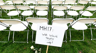 A protest sign stands in front of a row of chairs as family members of victims of the MH17 crash lined up empty chairs for each seat on the plane during a protest outside the Russian Embassy in The Hague, Netherlands March 8, 2020.