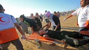 Des auxiliaires médicaux palestiniens portent un protestataire blessé lors des manifestations dans le sud de Gaza, vendredi 10 août 2018.