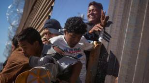 Los migrantes, que forman parte de una caravana de miles de habitantes de Centroamérica que intentan llegar a los Estados Unidos, regresan a México después de ser golpeados por gas lacrimógeno por parte de la Agencia de Aduanas y Protección Fronteriza de EE. UU. Después de intentar cruzar ilegalmente el muro fronterizo hacia los Estados Unidos en Tijuana. , México 25 de noviembre de 2018.