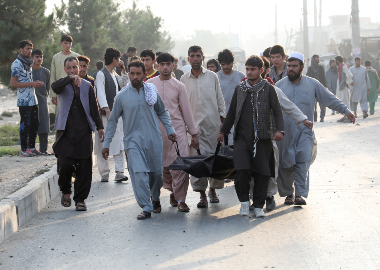 Afganos cargan el cuerpo de una persona asesinada en Kabul.